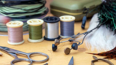 Photo Fly tying equipment and materials in preparation of making trout flies
