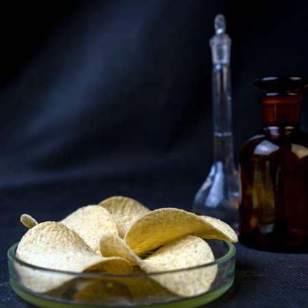 Chips and medical laboratory flasks on black blue background