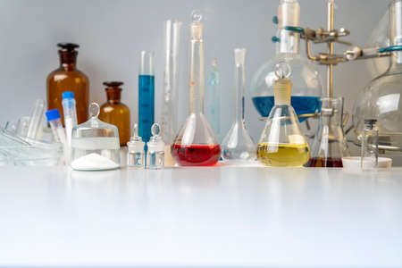 Flasks, test tubes and laboratory glassware with solutions of different colors on the table in the laboratory. Foto de archivo