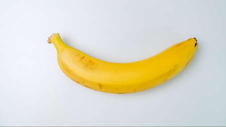 Single banana against white background Foto de archivo