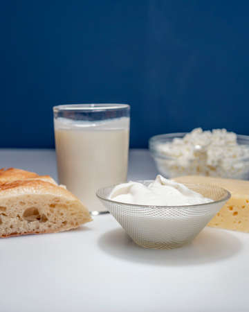 Photo still life with dairy products, milk, bread and cheese on a white background