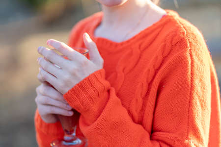 Photo orange knitted sweater dressed on a girl close-up