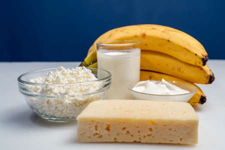 Photo still life with banana and dairy products milk, bread and cheese on a white background Foto de archivo