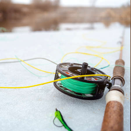 Photo winter fly fishing picture. Fly rod and reel on snowy river bank.
