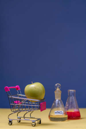 Photo a green apple in a mini-cart next to there are flasks with nitrates. Eco products concept in supermarket. Foto de archivo