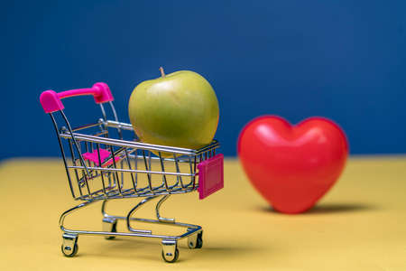 Photo Green Apple in mini shopping cart on yellow table. Food for Health, lose weight and money saving for Healthcare concepts