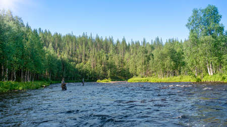 Fly fishing summer fishing in a mountain river. Beautiful nature, forest and sunset. Foto de archivo