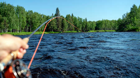 Fly fishing rod in fisherman hand. Fishing on the mountain river. Summer Activities.