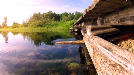 Photo wooden pier for boats at sunset with reflection in the lake.
