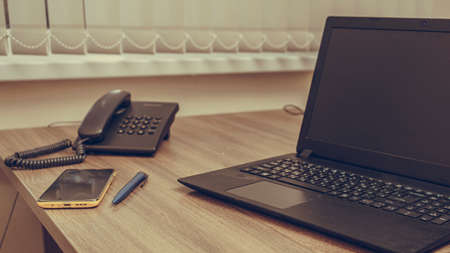Close up. Office, workplace of a businessman: laptop, phone, pen on the table.