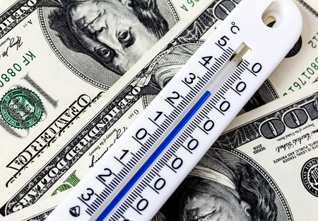 medical bills: The thermometer lying on the dollar, showing a high temperature.