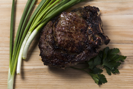 Ostrich steaks with sharp onions on a light background