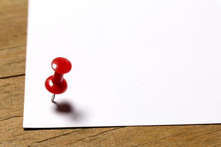 paper pin: white paper attached to a wooden surface weathered red pin Stock Photo