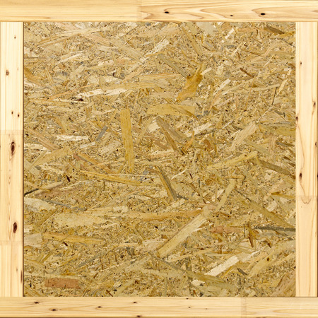 sandy brown: Oriented Strand Board. Building material. Wooden panel made of pressed sandy brown wood shavings as background closeup Stock Photo