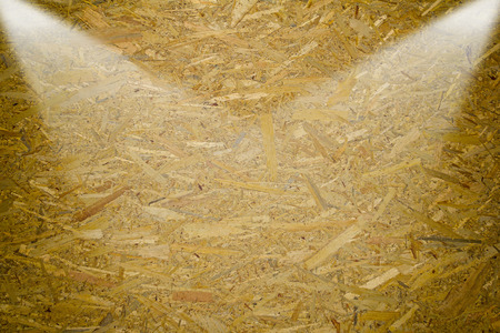 oriented: Oriented Strand Board. Building material. Wooden panel made of pressed sandy brown wood shavings as background closeup by two lights