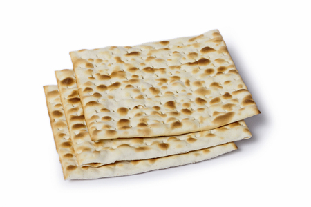 Multiple machine made matza flatbreads lying one over another, composition isolated over the white background