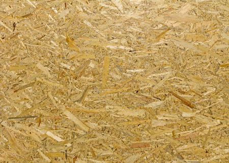 oriented: Oriented Strand Board. Building material. Wooden panel made of pressed sandy brown wood shavings as background closeup Stock Photo