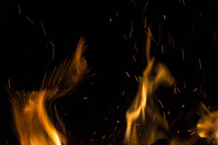 glow pyrotechnics: Burning fire with fiery orange flames, sparks and embers exploding into the air on a dark background with copy space