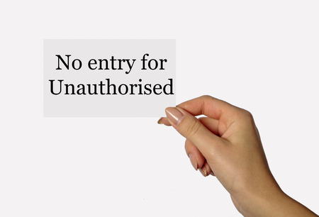 unauthorized: Beautiful hand of a young girl holding a card on a white background with an inscription no entry for unauthorized Stock Photo
