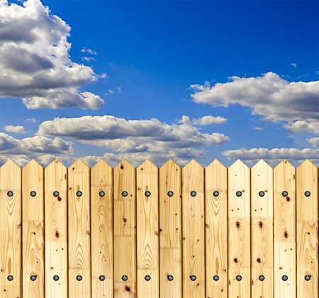 Detail of a wooden fence built with spiky wooden boards against a blue sky Stock Photo