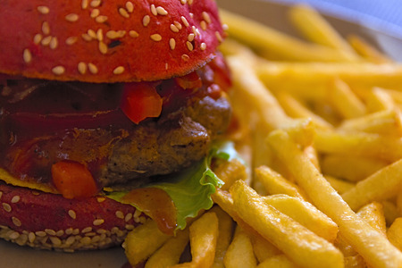 tangy: Fresh, juicy burger with tangy Mexican Tabasco sauce and French fries closeup. Fast food background. Stock Photo