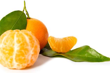 Fresh tangerines and peeled fruit on white background.