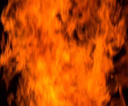 Background of fire. Texture fire flames  throughout the space. Fire red up close. The background with flames of fire. Stock Photo