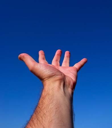splayed: A hand with fingers spread against the blue sky Stock Photo