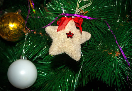 Christmas Toy furry star on the artificial Christmas tree Stock Photo