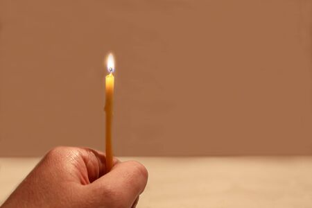 The hand holding a burning candle on a beige background