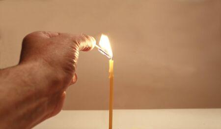 colores calidos: Mano con una cerilla enciende una vela en tonos c�lidos