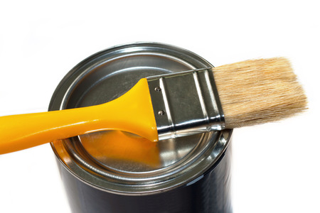yellow paint: Brush with yellow handle and closed paint pot isolated on white background