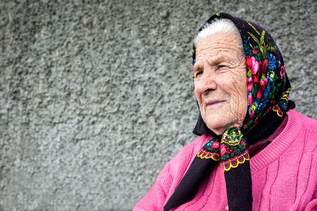 Goede nadenkend grootmoeder close-up zitten in de buurt van het huis
