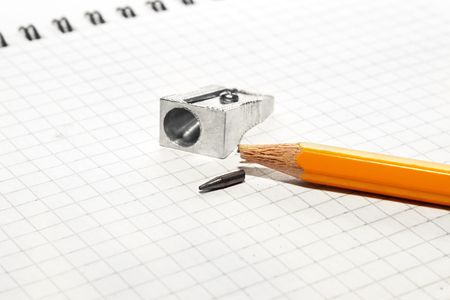 grafit: A broken pencil and a pencil sharpener on a notebook