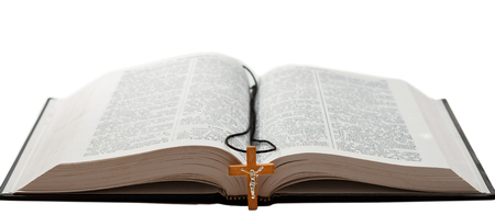 白い背景に隔離された本と十字架を開く