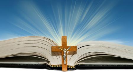 光の線と青の背景に木製の十字架を開いた本