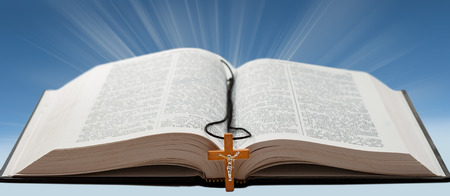 Open book with a wooden cross on a blue background with rays of light