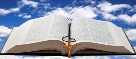 Open book with a wooden cross against a blue sky with white clouds