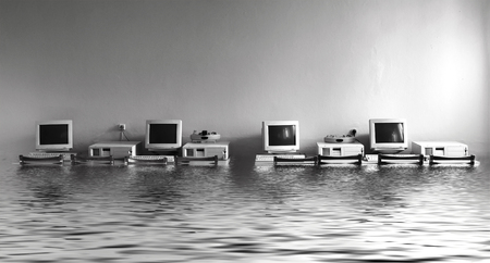 Black and white photo cabinet with computers flooded with water Stockfoto
