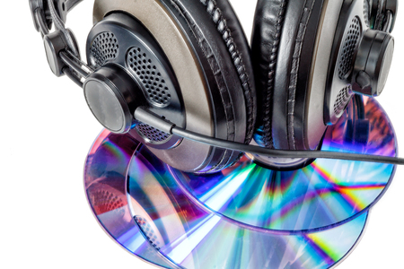 Compact discs and headphones close up isolated on white background