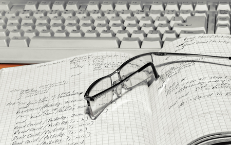 Notebook with glasses and a computer keyboard close-up Archivio Fotografico - 126202378