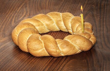 Wicker bread and a burning candle on a wooden background Stockfoto