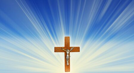 Wooden cross crucifix in the rays of light on a blue background 版權商用圖片