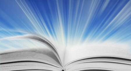 Glowing open book in the rays of light on a blue background