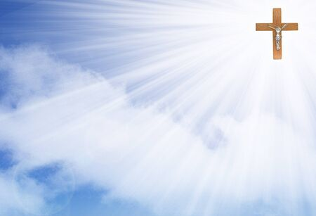 Wooden cross crucifix in the rays of light on a blue background with cloud