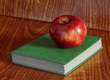 Apple and book on a wooden background