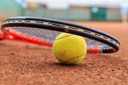 raqueta de tenis: Pelota de tenis y raqueta en la cancha de tenis de arcilla