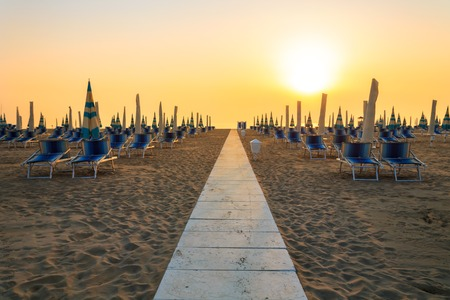 blue romance: At sunrise sunbeds on the beach in Rimini, Italy Stock Photo