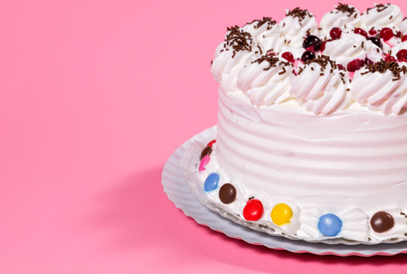 fun background: Tasty creamy birthday cake colorful candy adorned on pink background