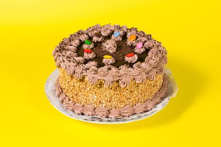 chocolate birthday cake: Tasty chocolate and hazelnut birthday cake colorful candy adorned on yellow background